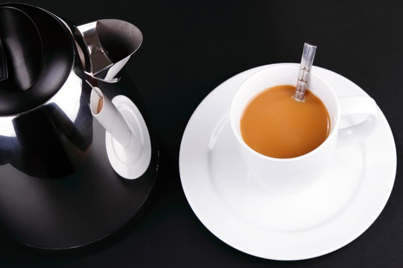 A quiet stainless steel kettle and a cup of coffee.