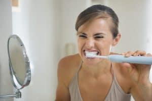 Brushing teeth with a quiet electric toothbrush.