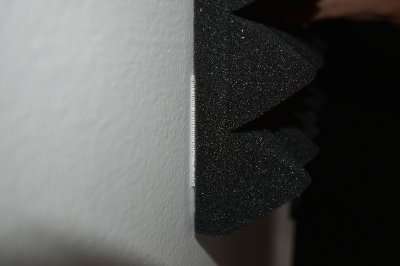 Using Command Strips to hang acoustic foam panels. Damage-free option.