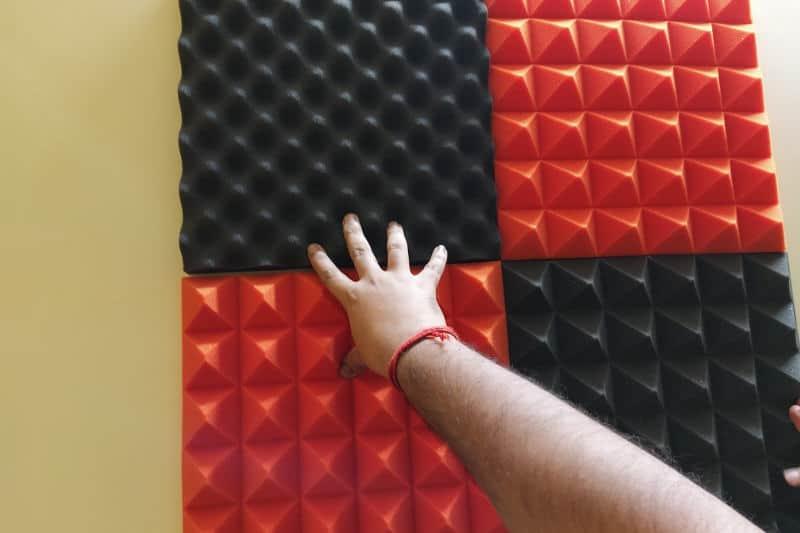 Installing acoustic foam panels on walls.